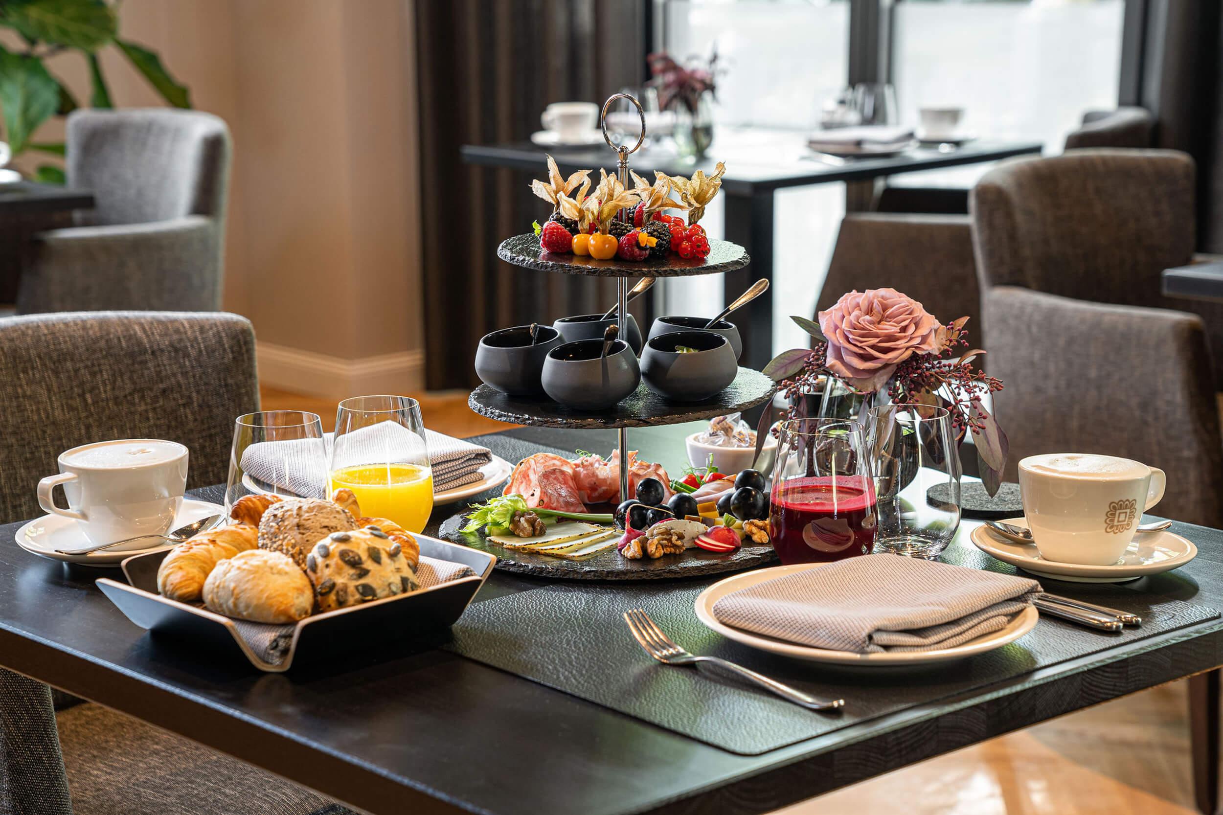 Fruehstueck im Fruehstueckssalon des Hotels. Es zeigt einen gedeckten Tisch mit angerichtetem Fruehstueck. Im Hintergrund sind weitere gedeckte Tische zu sehen. Die Datei ist ein Foto im JPEG-Format.