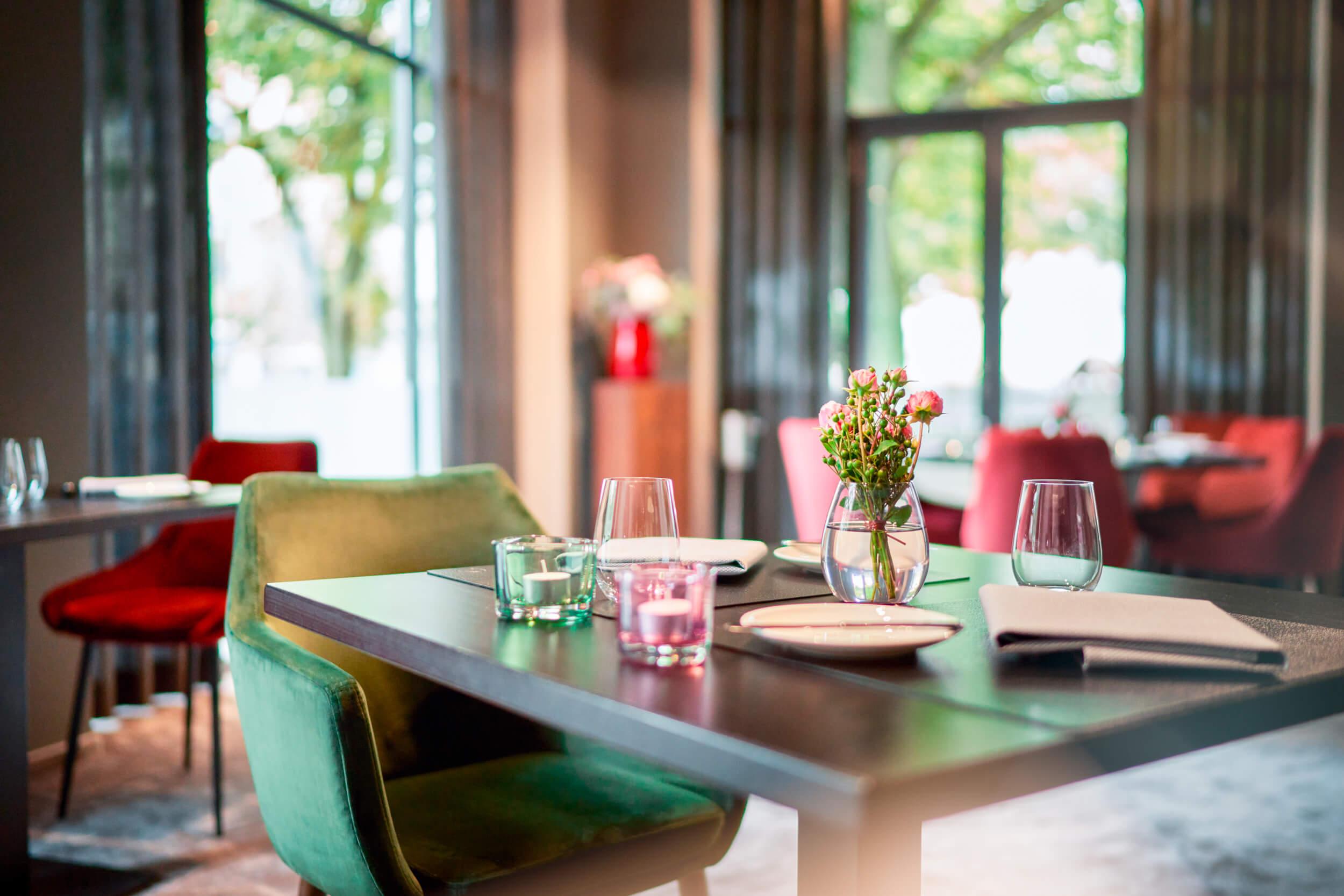 Gourmet-Restaurant ESPLANADE – Tisch. Es zeigt im Vordergrund einen gedeckten Tisch im ESPLANADE Gourmet-Restaurant. Der Hintergrund ist unscharf und weitere Tische sowie grosse Fenster mit einem Ausblick ins Gruene sind darin zu sehen. Die Datei ist ein Foto im JPEG-Format.