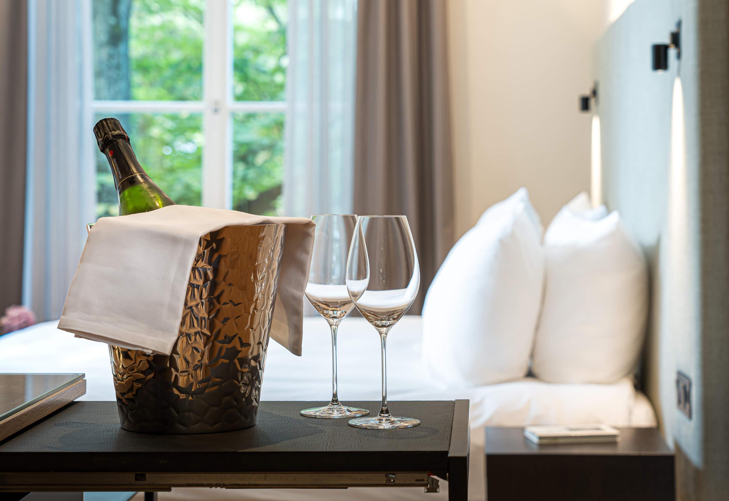 Hotelzimmer mit Champagner und Wein. Es zeigt im Vordergrund eine gekühlte Flasche Champagner mit zwei Weinglaesern auf einer dunklen Ablage. Im Hintergrund ist das Hotelzimmer unscharf zu sehen mit einem grossen Fenster mit Blick ins Gruene links im Hintergrund und einem Doppelbett davor mit Kissen auf der rechten Seite. Die Datei ist ein Foto im JPEG-Format.