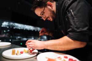 Chefkoch Silio Del Fabro beim Anrichten in der Kueche des Restaurants. Es zeigt rechts Chefkoch Silio Del Fabro der lächelnd auf den Teller auf der Theke links im Bild schaut und das Gericht darauf mit beiden Haenden anrichtet. Die Datei ist ein Foto im JPEG-Format.