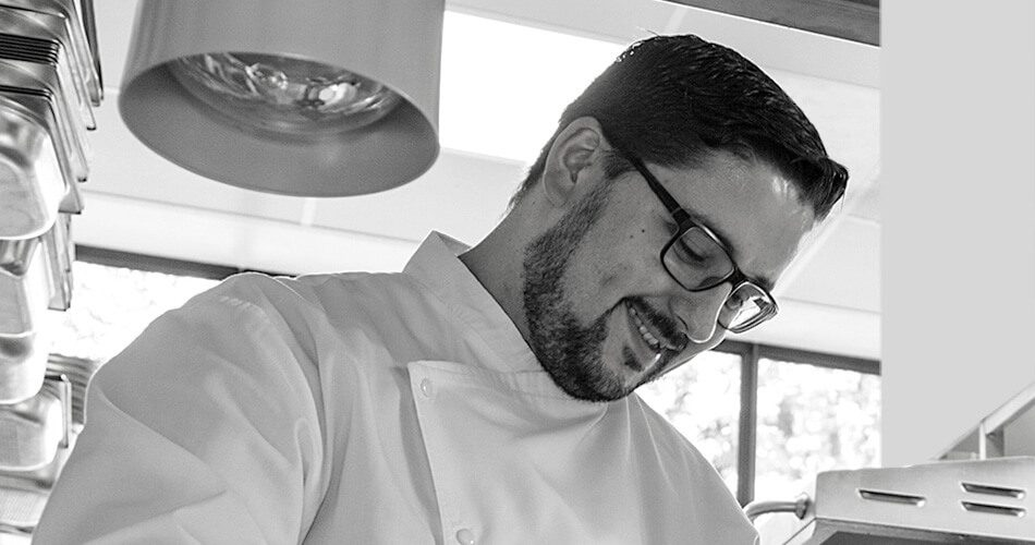 Silio Del Fabro – Schwarz-Weiss-Foto. Das Bild zeigt Silio Del Fabro lächelnd während der Zubereitung in der Kueche. Die Datei ist ein Foto im JPEG-Format.