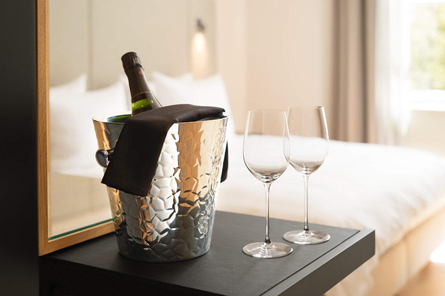 Hotelzimmer mit Champagner und Weinglaesern. Es zeigt im Vordergrund eine gekühlte Flasche Champagner mit zwei Weinglaesern auf einer dunklen Ablage. Im Hintergrund ist das Hotelzimmer unscharf zu sehen mit einem grossen Fenster mit Blick ins Gruene rechts im Hintergrund und einem Doppelbett mit Kissen auf der linken Seite. Die Datei ist ein Foto im JPEG-Format.