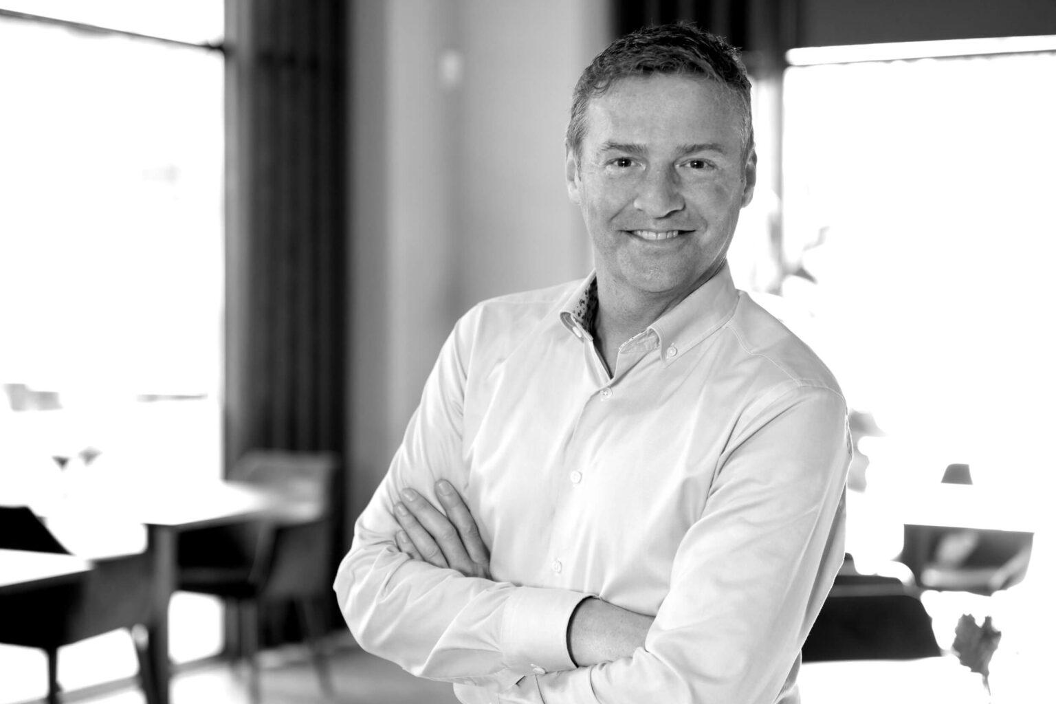 Jerome Pourchere – Schwarz-Weiss-Foto. Das Bild zeigt Jerome Pourchere lächelnd angelehnt an eine Wand. Die Datei ist ein Foto im JPEG-Format.